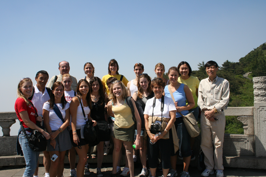 A group of students and professors standing atop a mountain in China